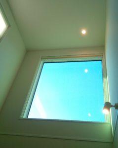 わが家の吹き抜けリビング。吹き抜け窓が一枚の壁画のように空を映し出してくれます。